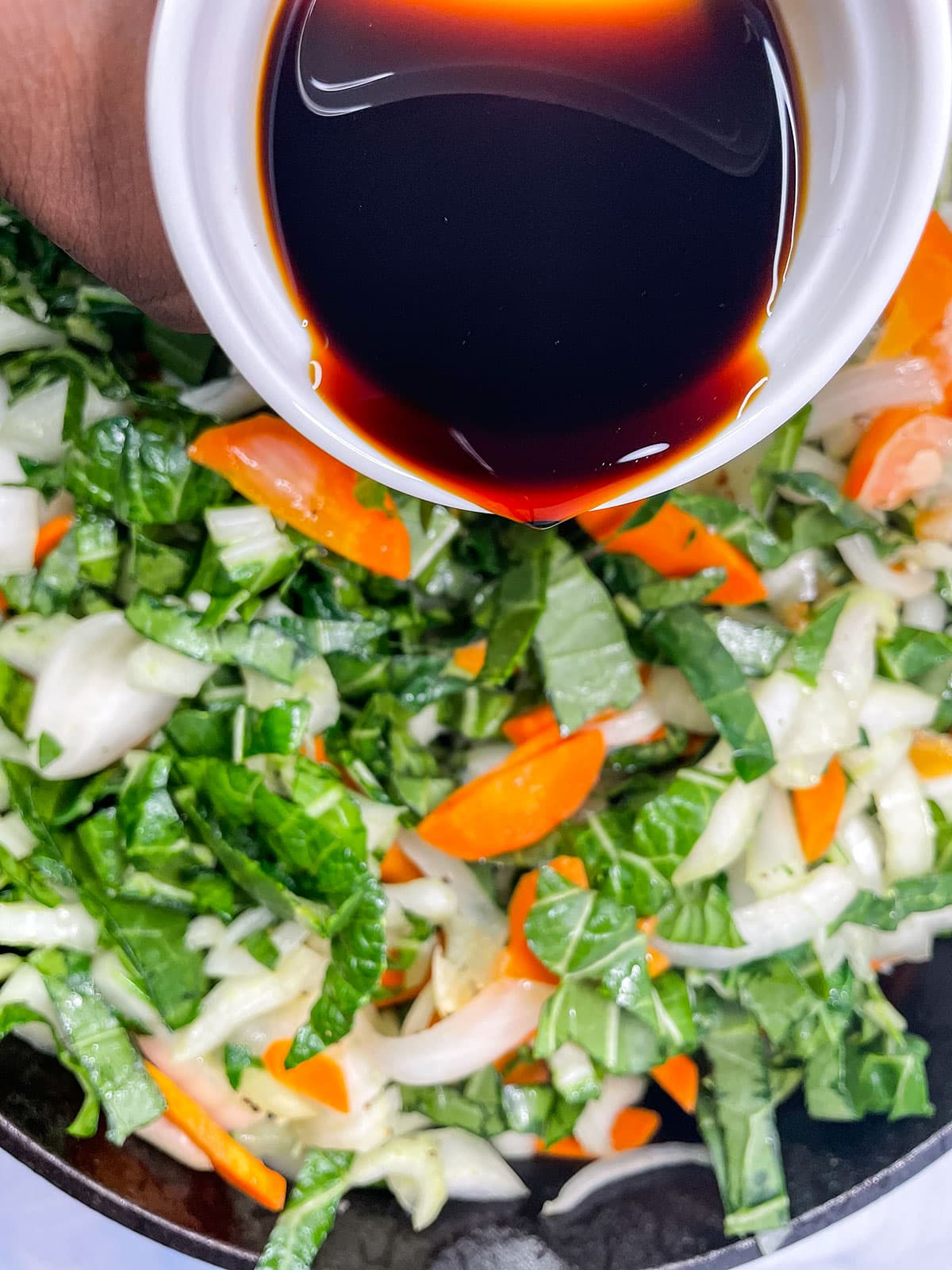chop suey cooking and pouring tamari over it.
