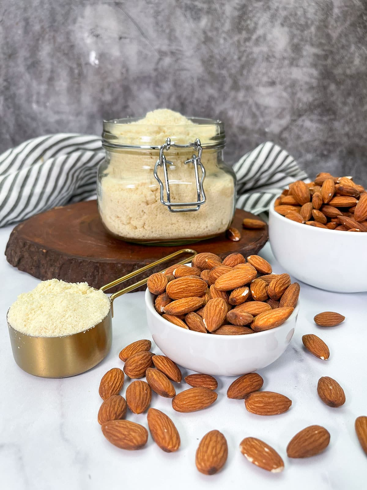 almond flour, almond in white bowl, and golden measuring cup