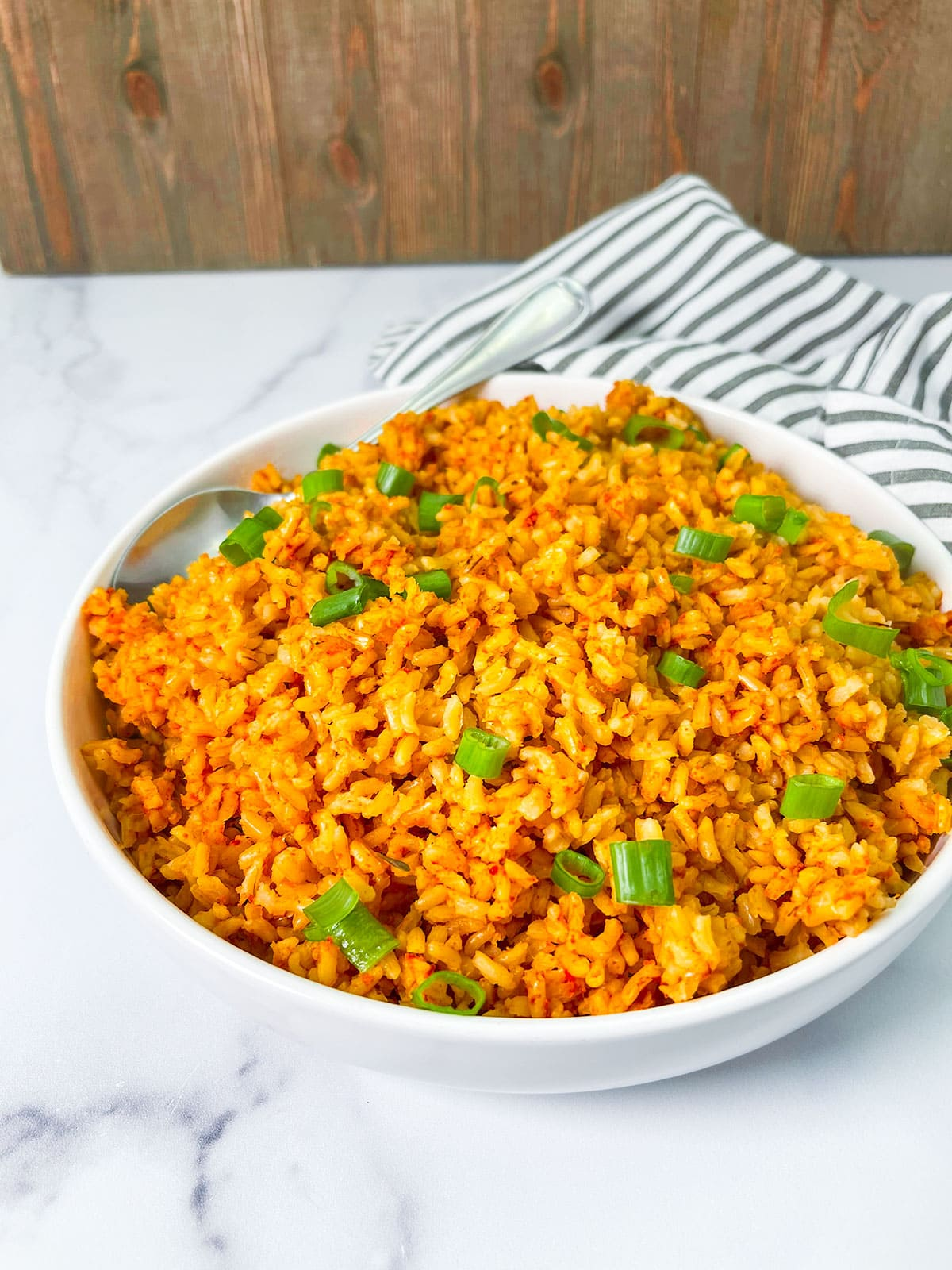 jollof rice in a white bowl on a white background with a stripe napkin