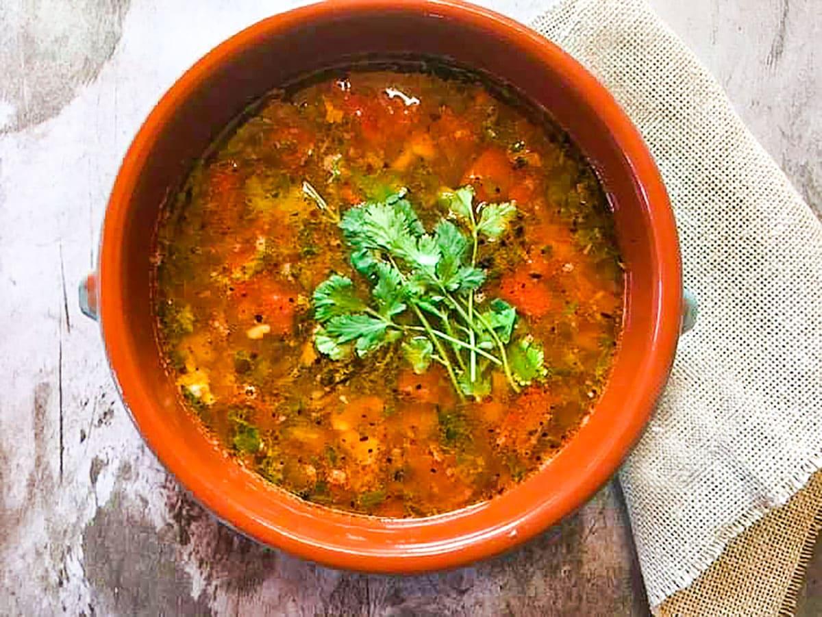 vegan tomato rasam overlay in a clay pot