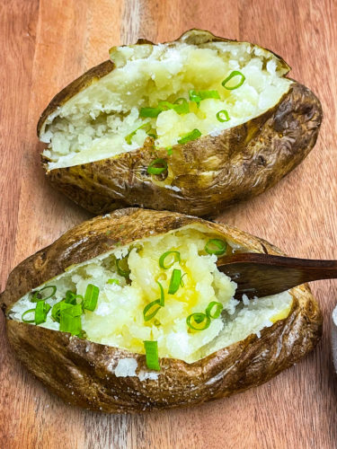 baked potatoes on a wooden background with. spoon