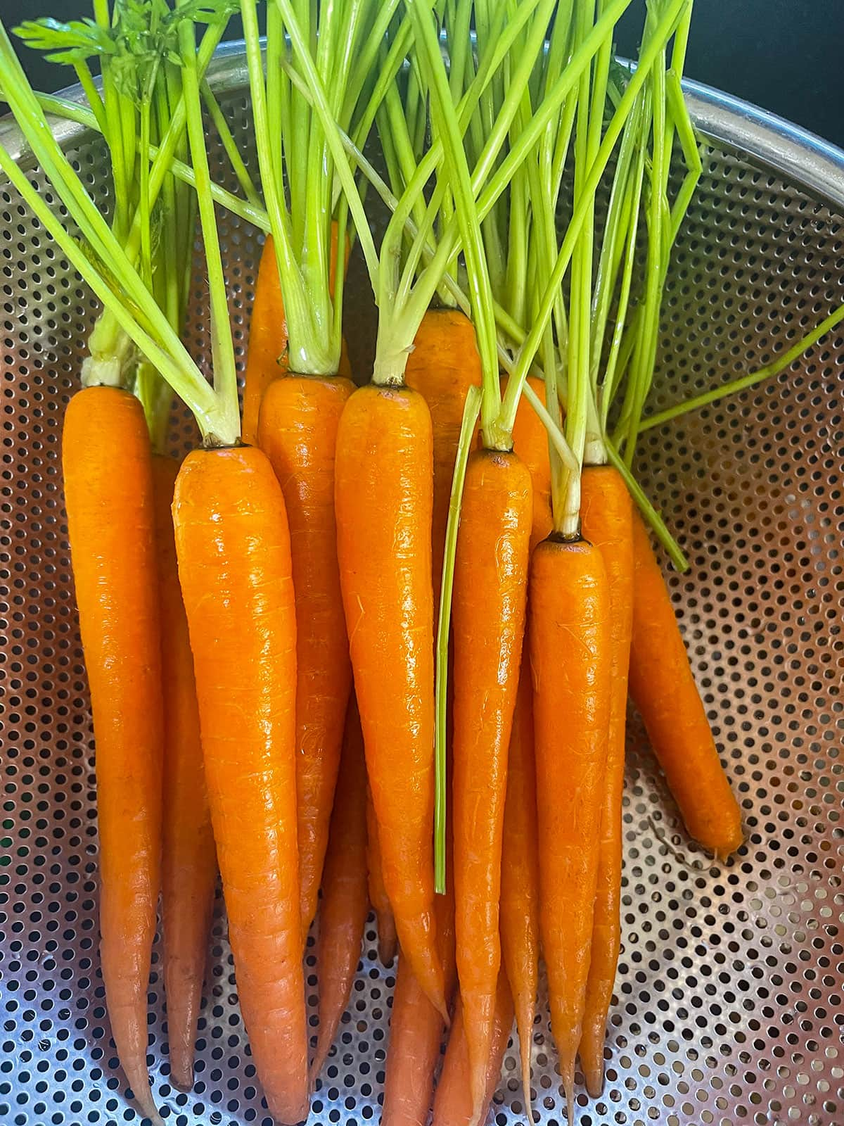 washing carrots in a colander