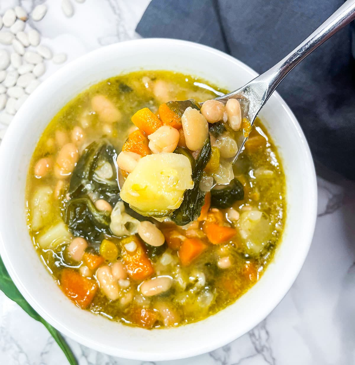 close up image of instant pot white bean soup with spinach in a white bowl with a spoonful on a white background