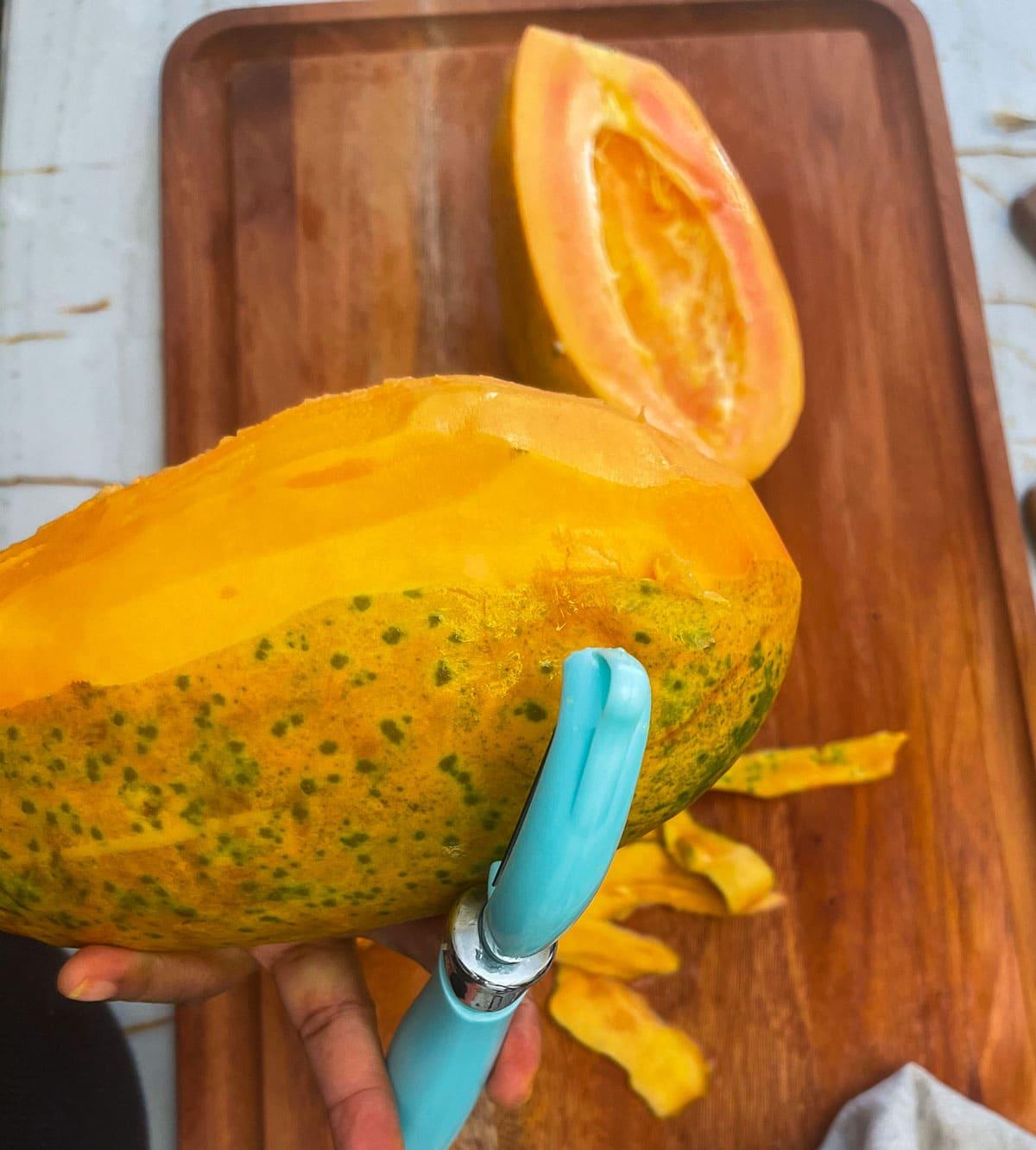 peeling papaya with a potato peeler