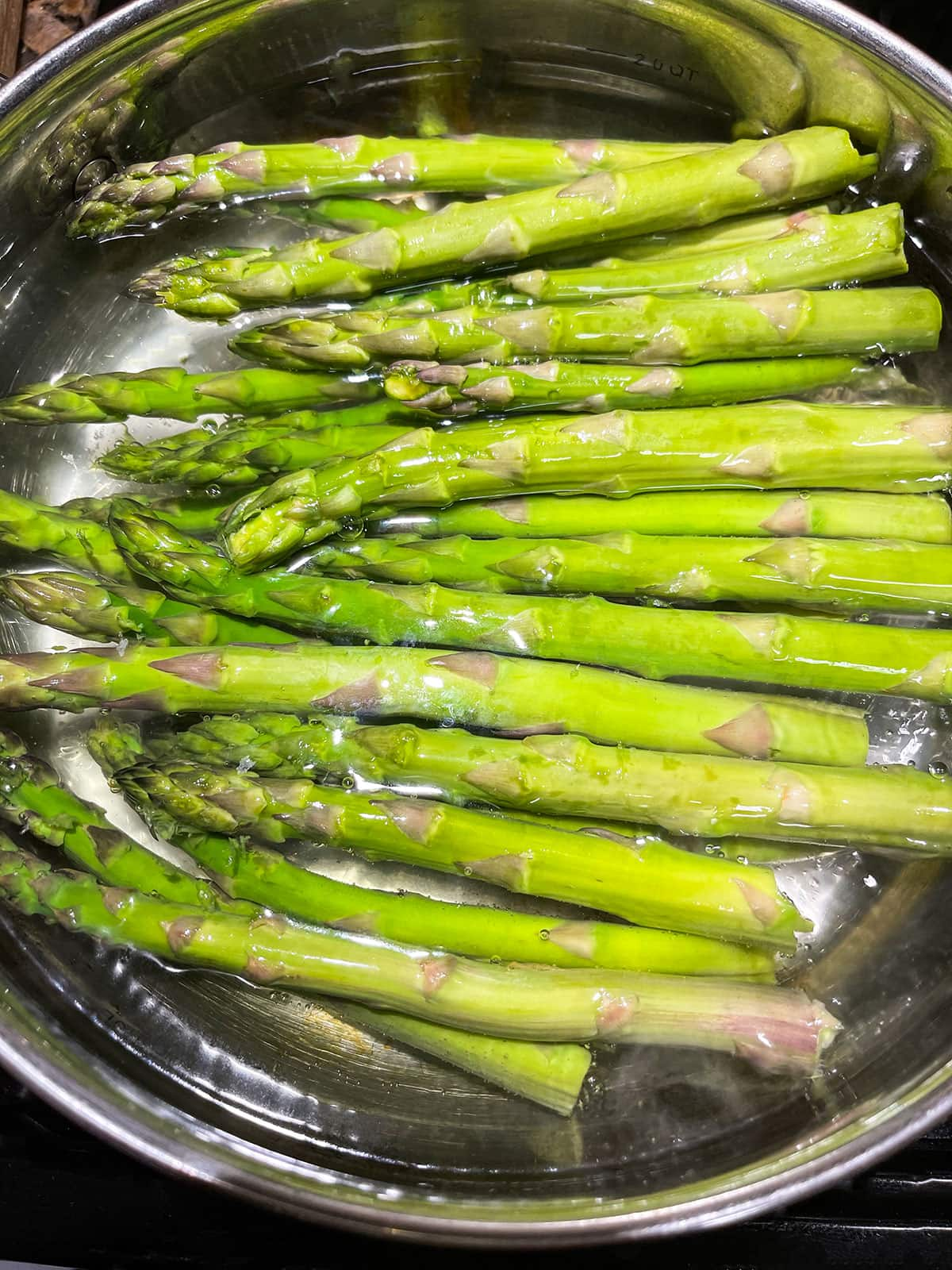 asparagus blanching in a saucepan of boiling water