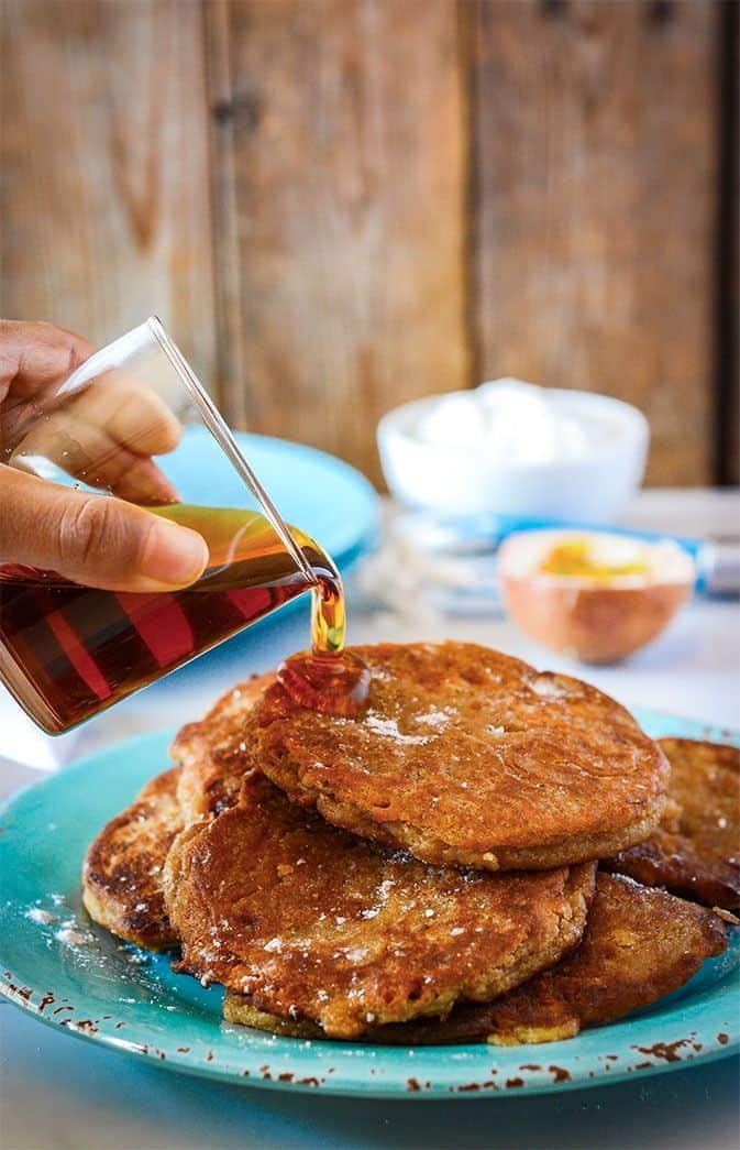 fritters on a blue plate with a hand pour syrup on them from a glass