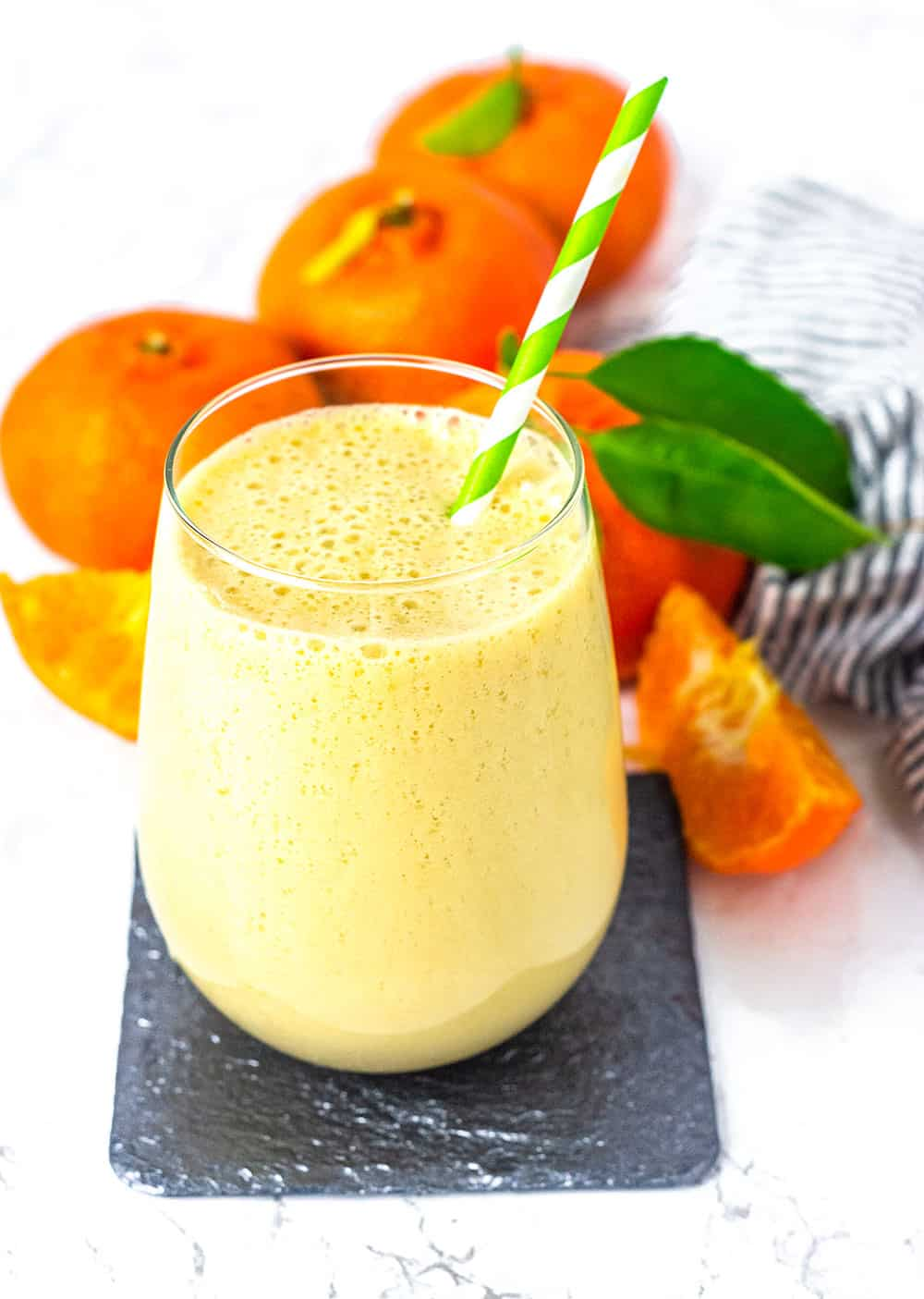 orange smoothie with green and white straw, on a black coaster with cut and whole oranges on a white background