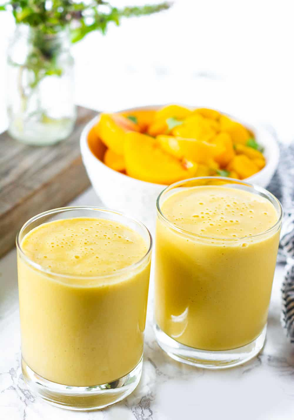 two peach mango smoothies with a bowl of fruit in the background