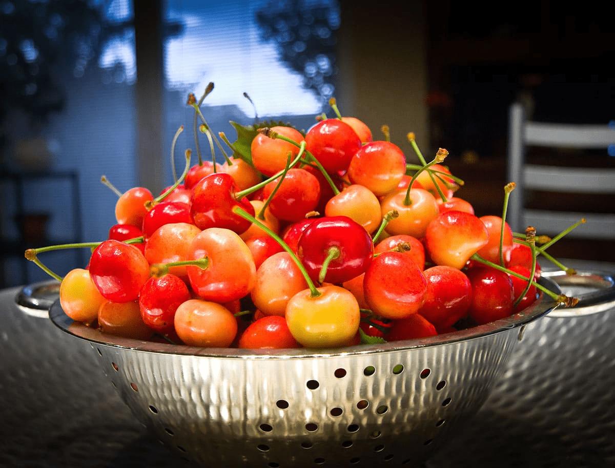 acerola cherries in a metal strainers