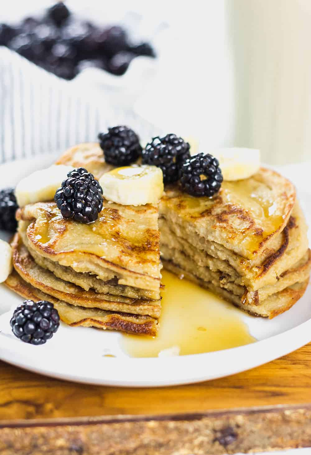 stack of pancakes with bananas, blueberries, and syrup on a white plate with a chunk cut out