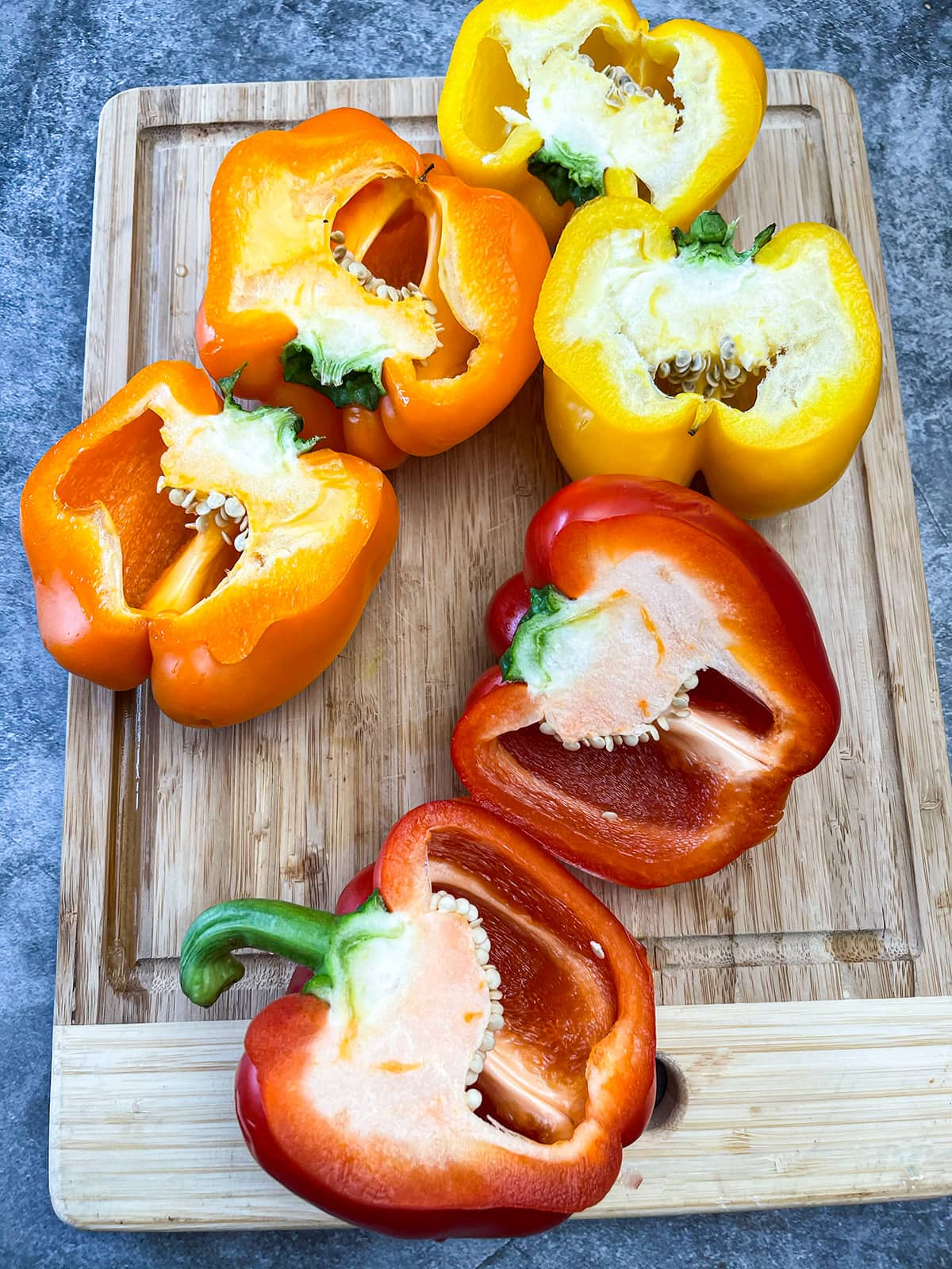 bell peppers cut into halves on cutting board
