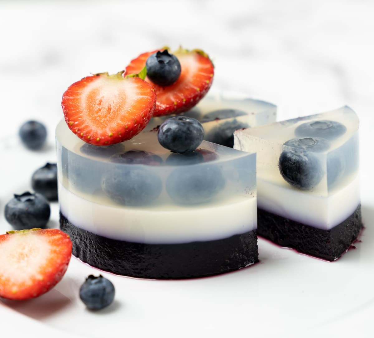 layered blueberry agar dessert topped with strawberries and blueberries with a slice cut out