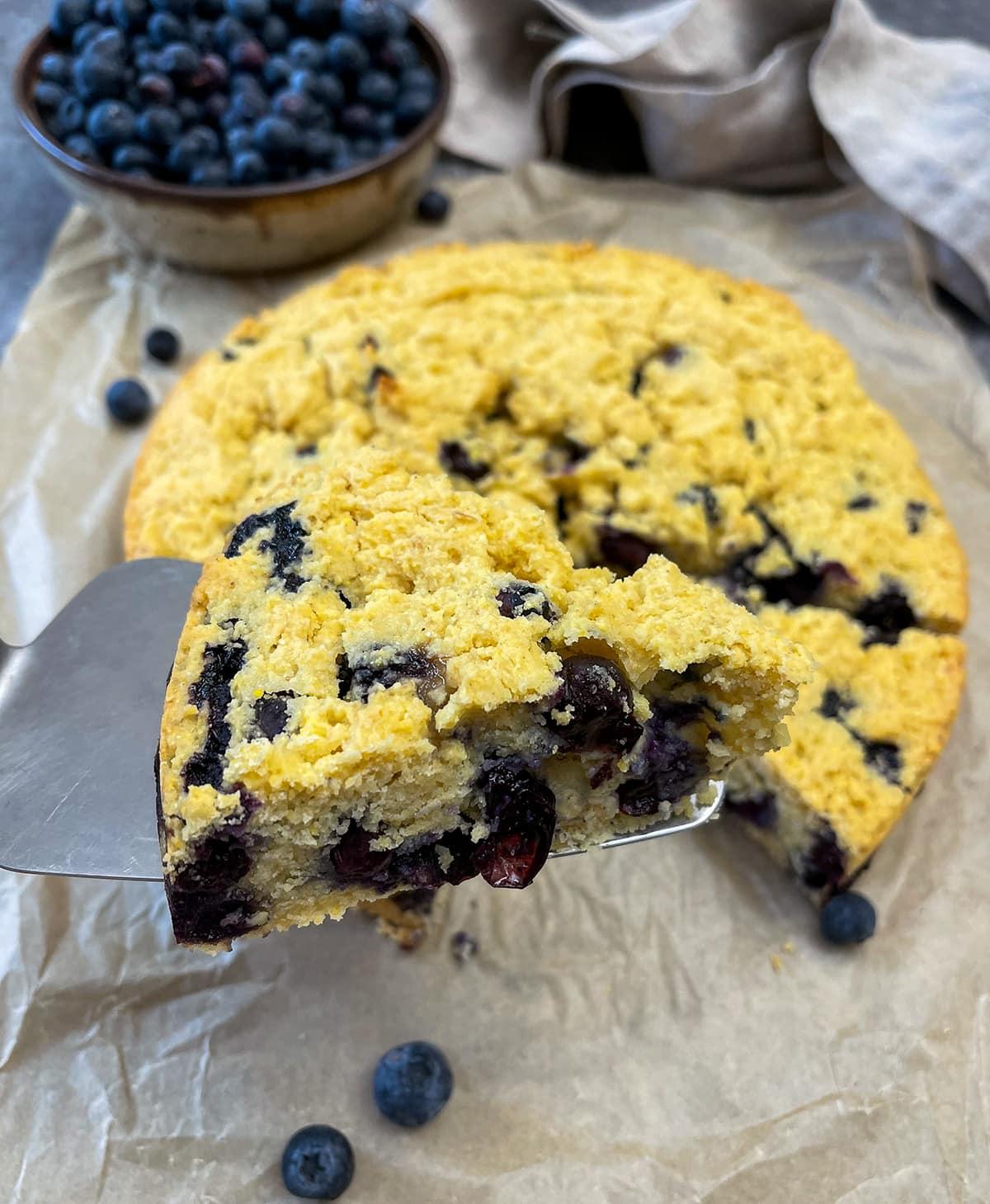 close up of blueberry cornbread, a slice on a server