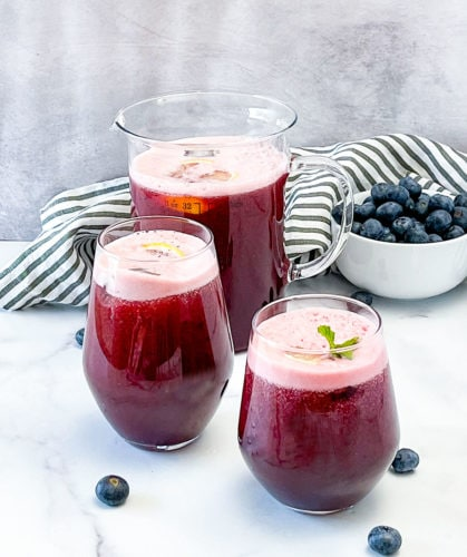 blueberry lemonade in 2 glasses and a pitcher or a white background