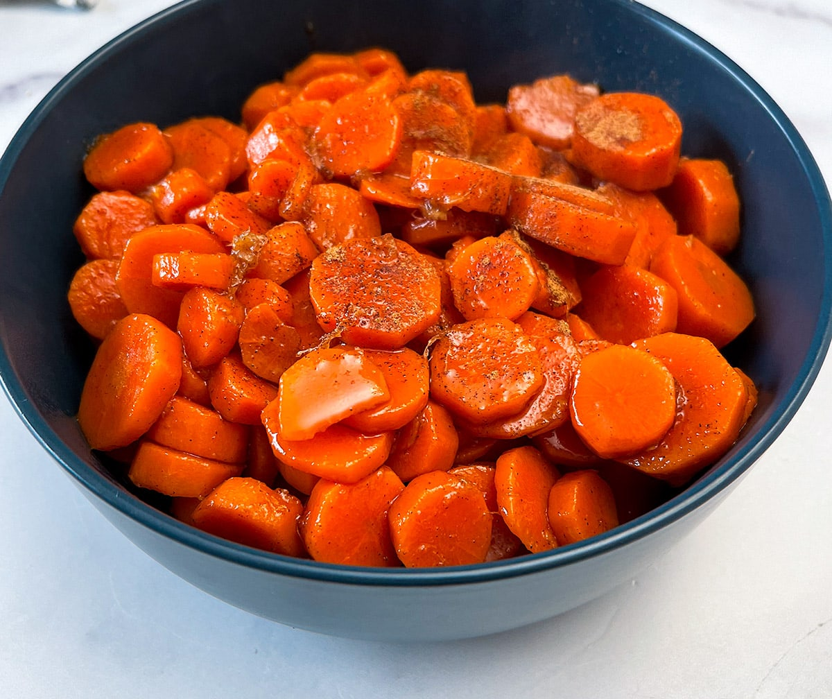 Candied carrot in a blue bowl on a white background