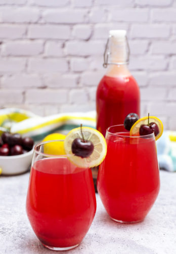 Cherry lemonade in glasses and bottles on a grey background