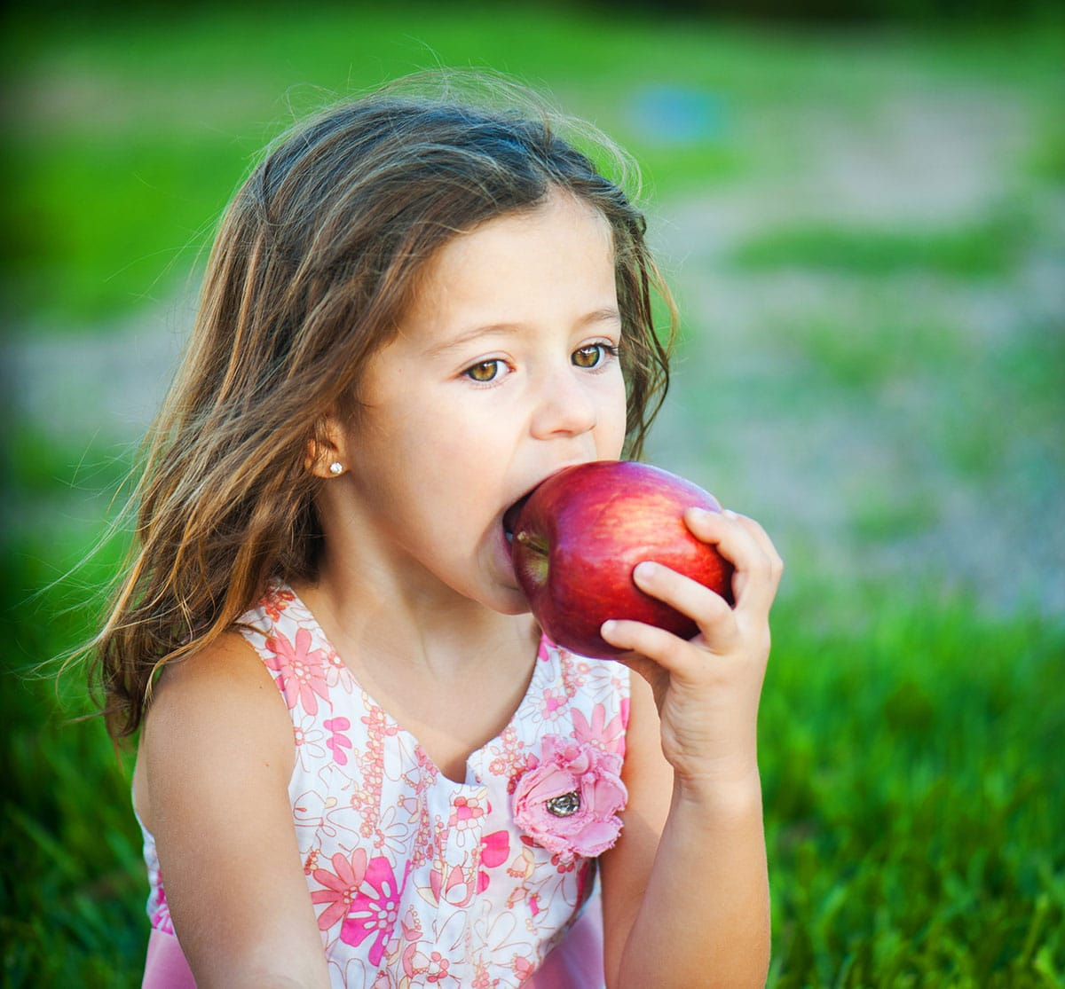 girl chewing an apple