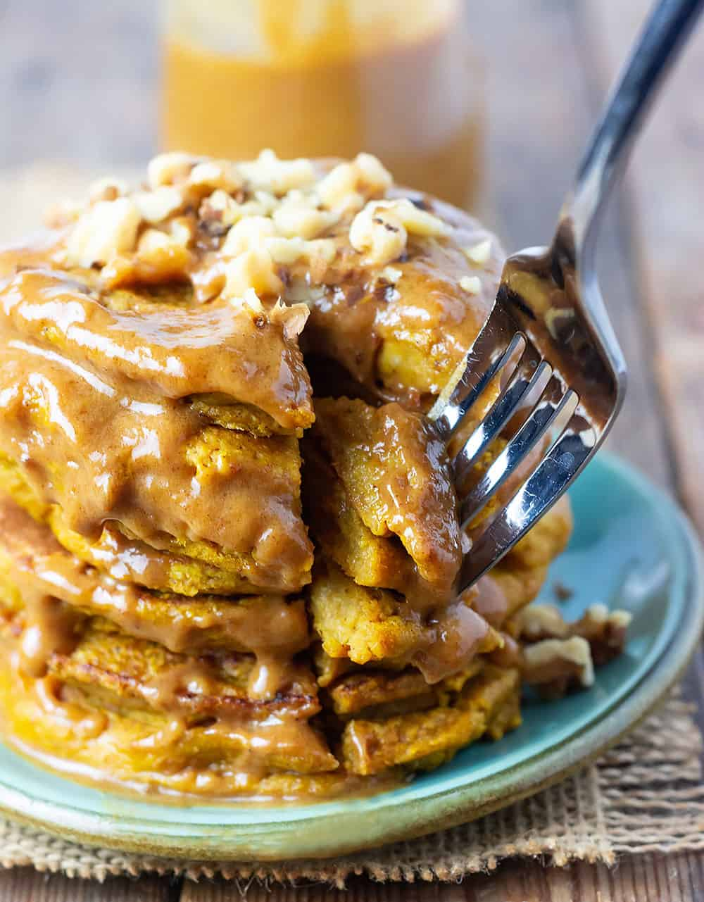 a stack of pumpkin pancakes with sauce drizzling down, and a cut out chunk being removed with a fork