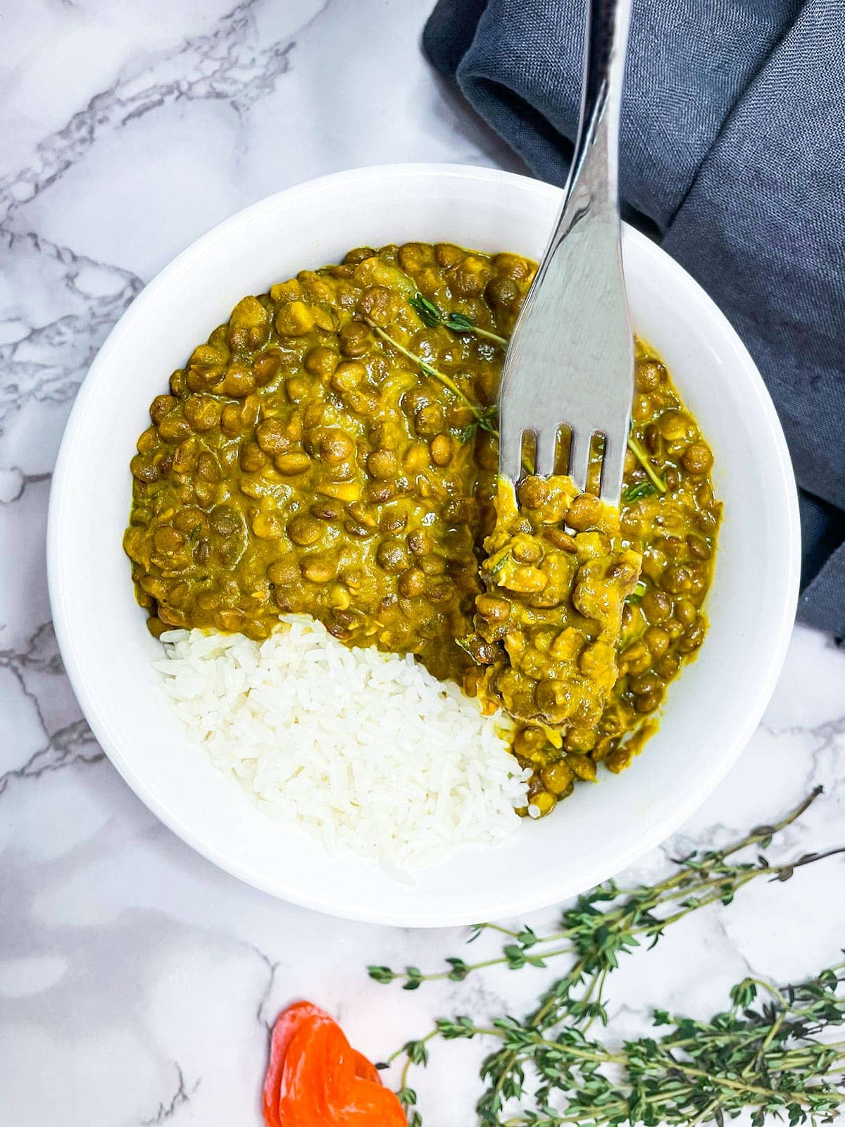 lentil curry and white rice in a white bowl with a fork