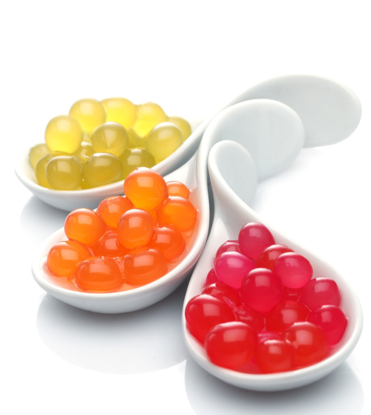 three varieties of popping boba in white spoons