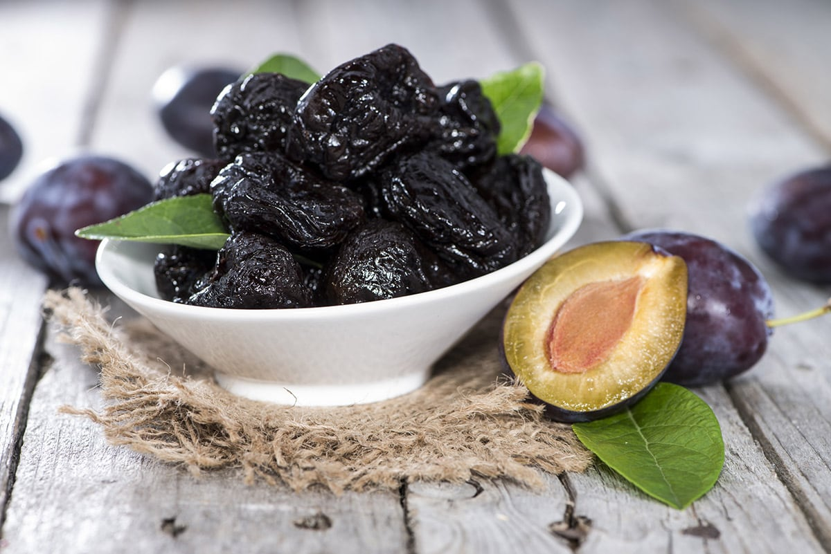 Prunes in a white bowl on a white wooden background