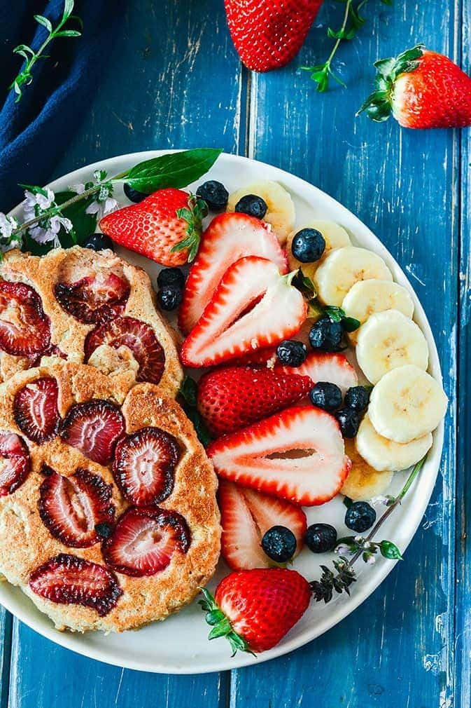 strawberry pancakes with fruit on the sides on a white plate