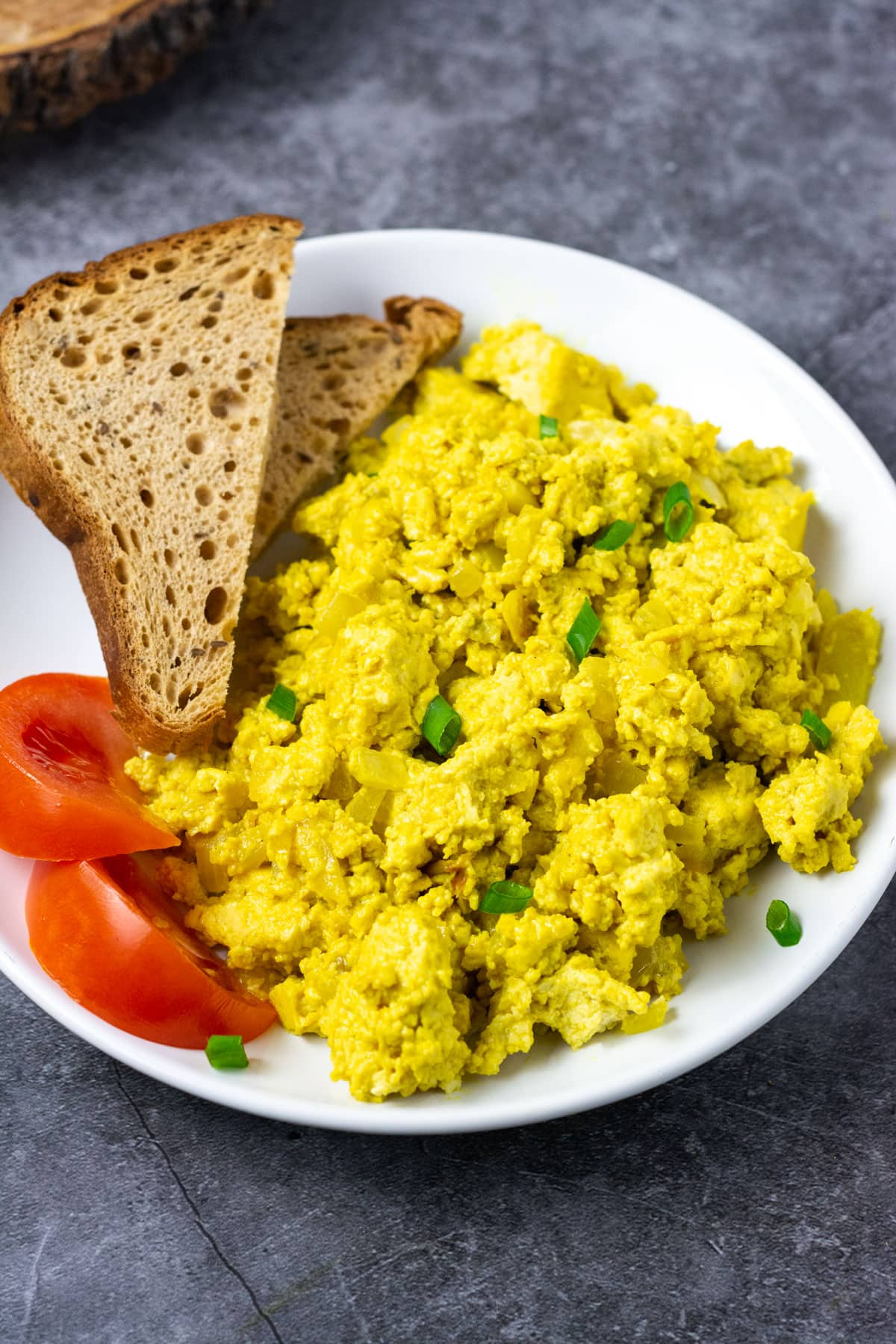 tofu scramble with pieces of tomato and bread on a white plate