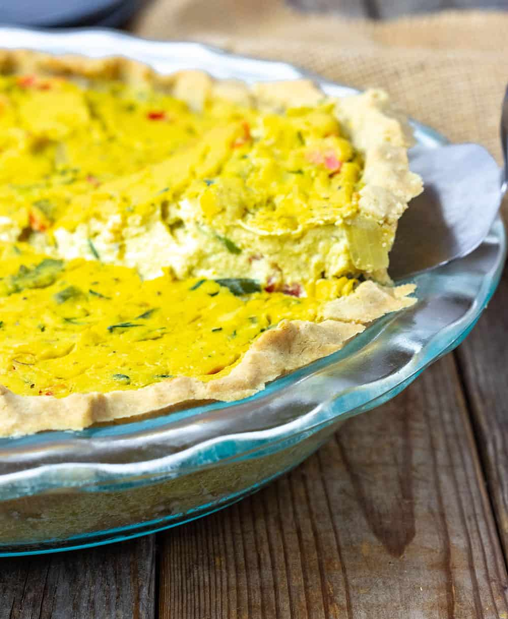 a slice being taken out of a quiche in a glass pie pan