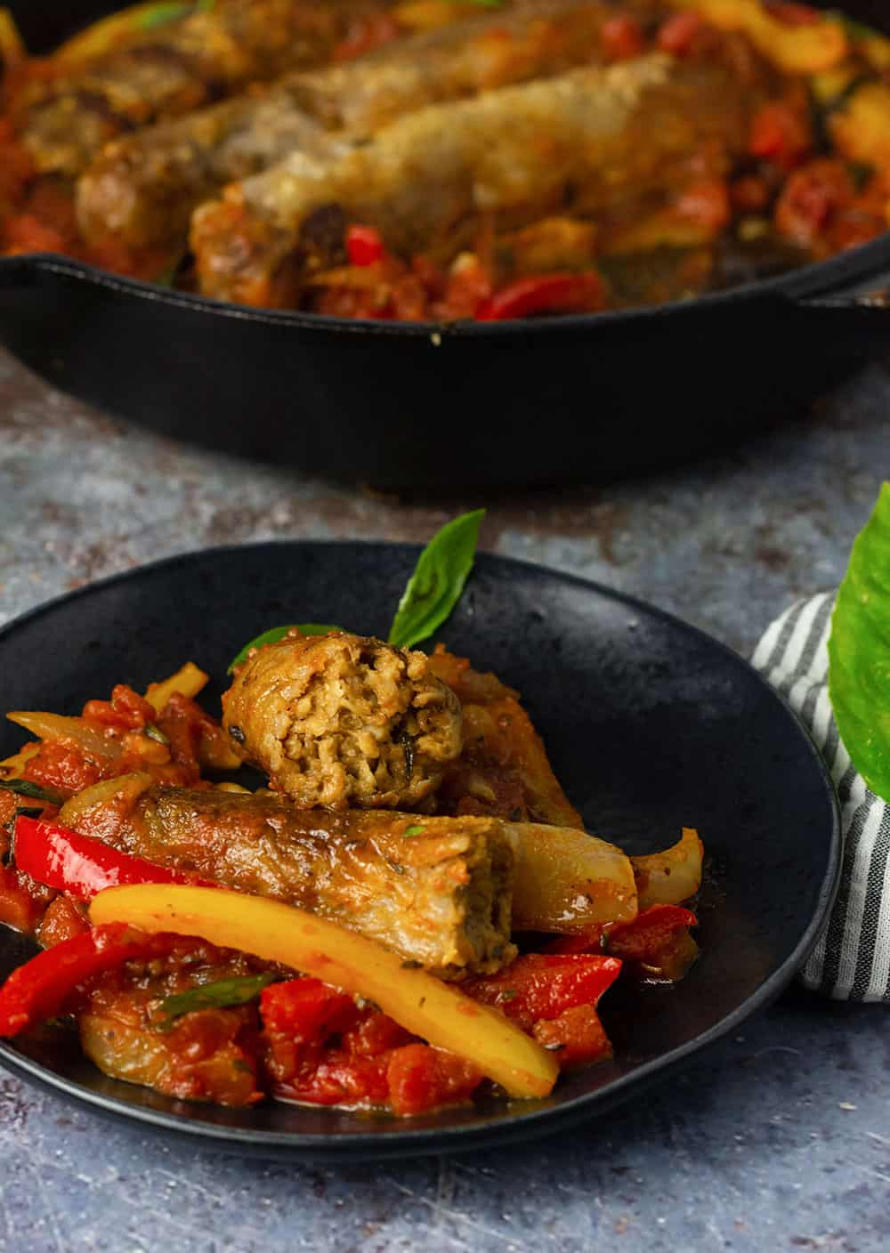 a black bowl with vegan sausage and peppers