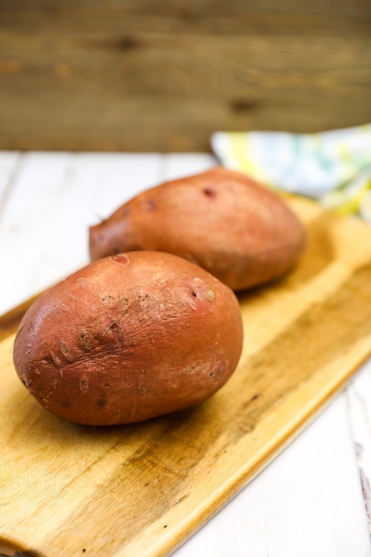 Two sweet potatoes on cutting board