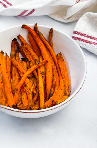 air fryer carrot fries in a white bowl on a white background with a red and white napkin