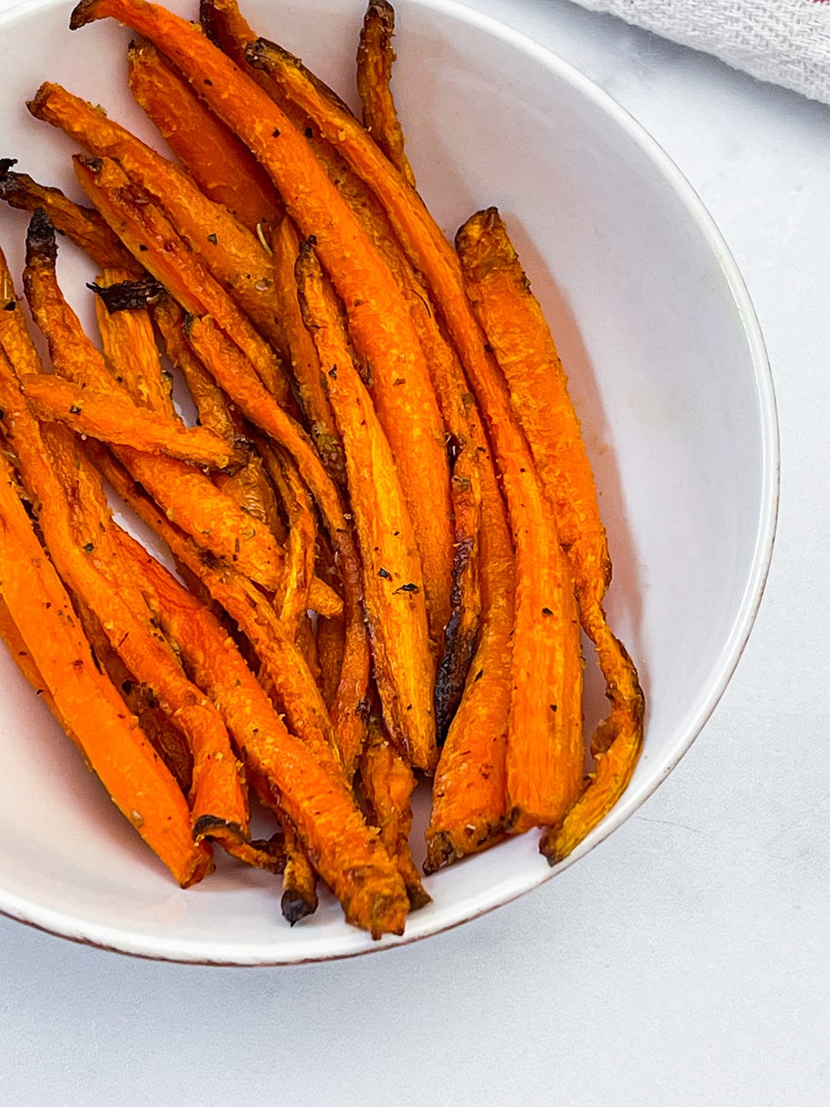 air fryer carrot fries in a white bowl on a white background