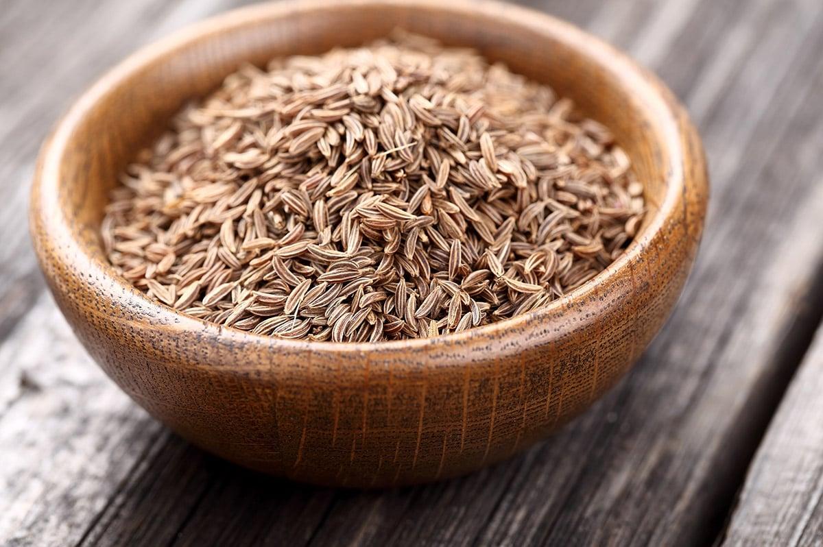 Caraway seeds in a wooden bowl on a wooden background