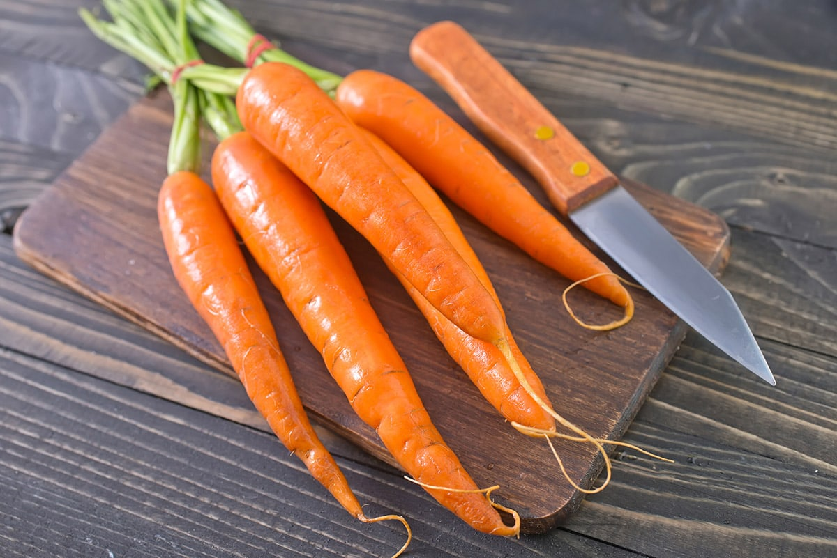 a bunch of carrot on a wooden cutting board