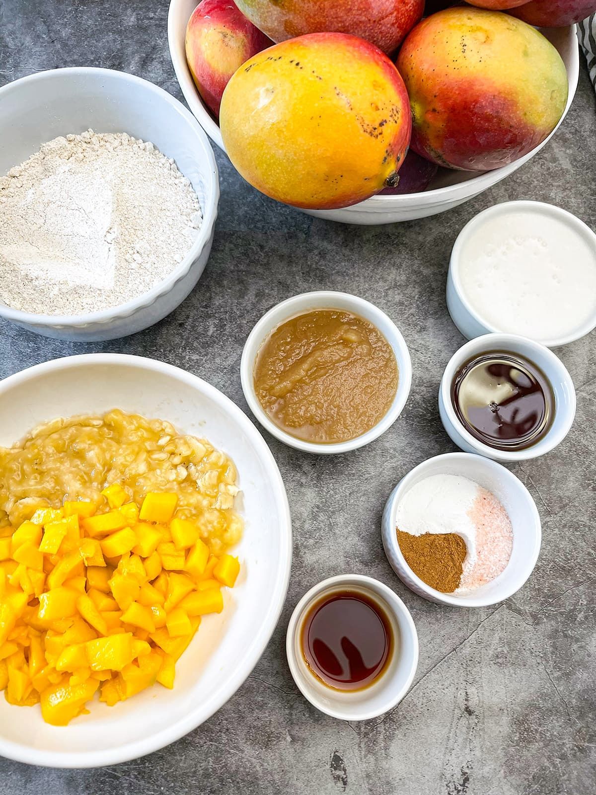 mango muffin ingredients on a grey background in white bowls