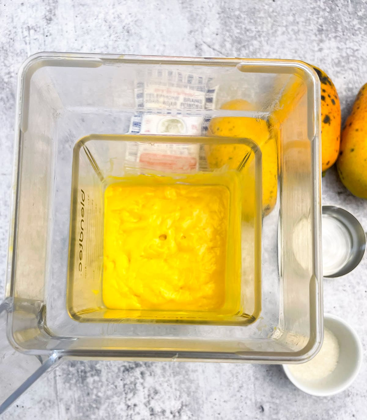 mango puree in the blender on grey background