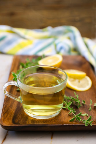 oregano tea on a wooden background with lemon slices and oregano leaves