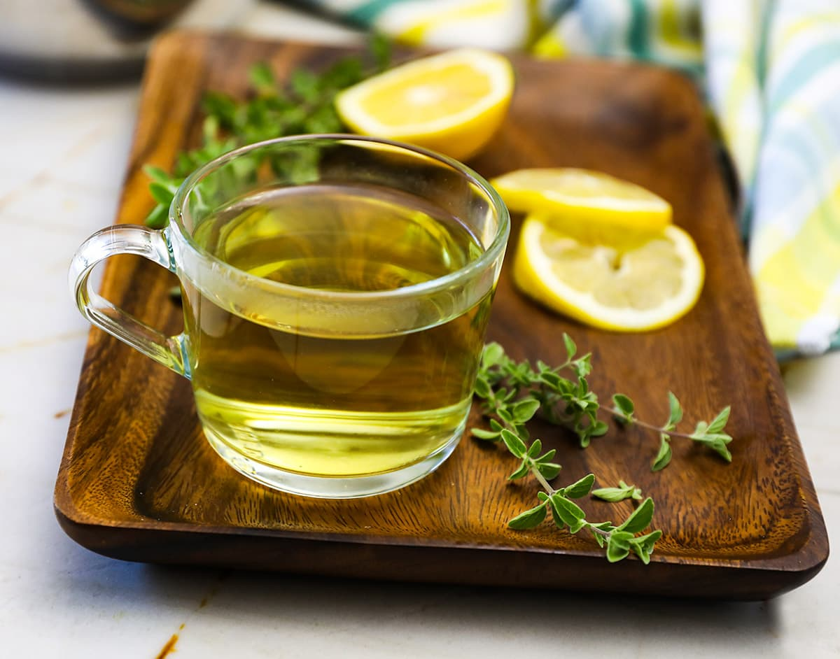 Oregano tea in a glass cup on a wooden background