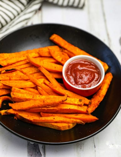 Sweet potato fries in a black bowl on a white background