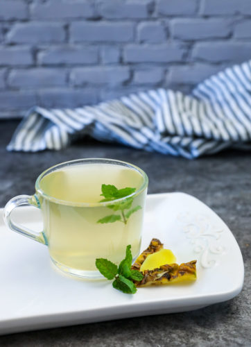 Pineapple peel tea on a white platter on grey background garnished with mint leaves, pineapple leaves and ginger slice