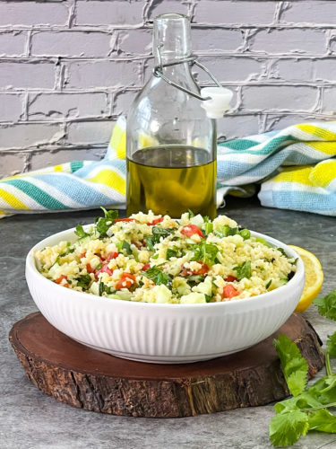 millet tabouli in white bowl on a wooden board