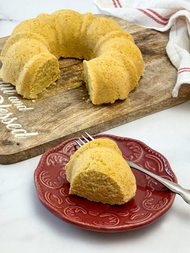 air fryer cornbread done in bundt pan on a wooden cutting board and a slice on a red plate