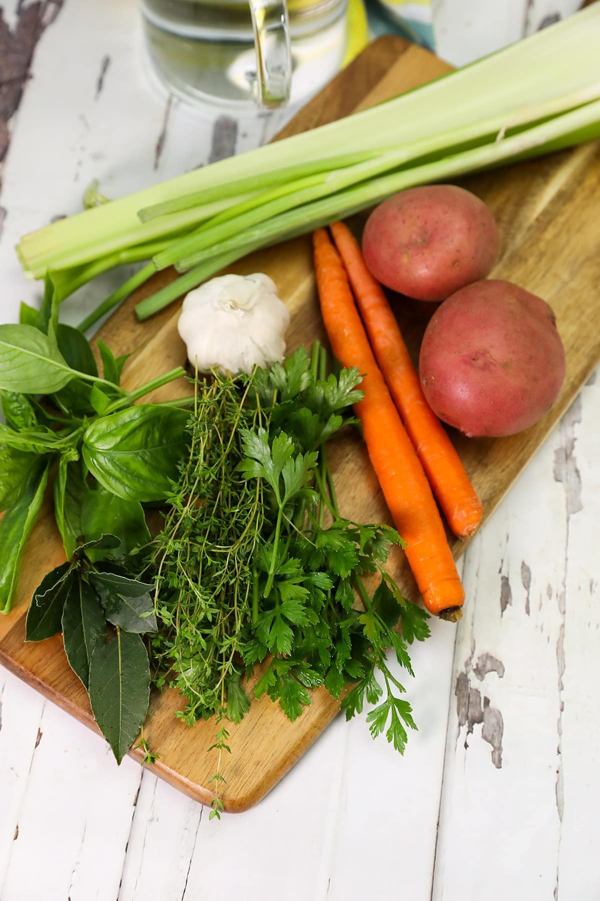 vegan broth ingredients, potato, carrot, celery herbs, garlic spices on a wooden background