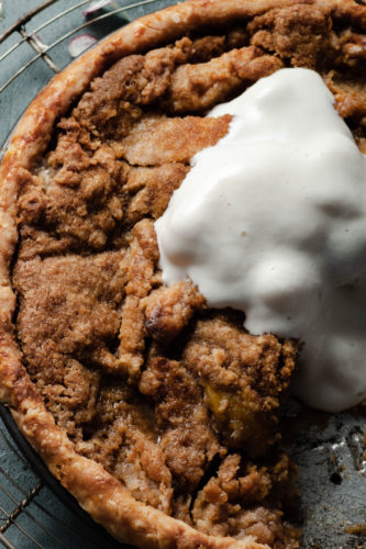 vegan apple pie with crumb topping in a glass pie plate with melted ice cream