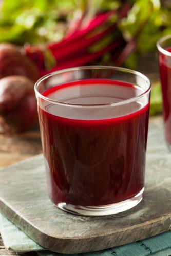 beet juice recipe in glass on wooden board