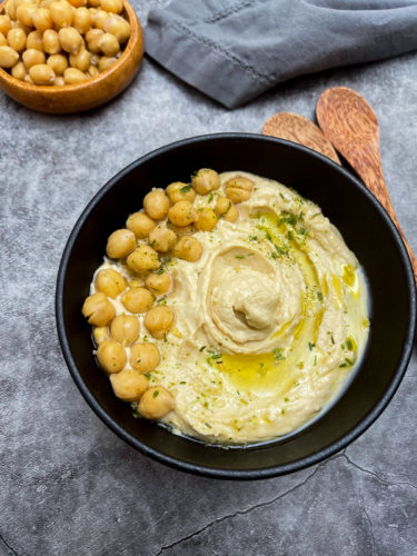 easy hummus recipe in a black bowl on a grey background with wooden spoons