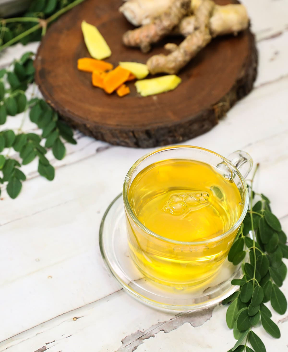 moringa tea with ginger and turmeric in a glass cup on a white wooden background