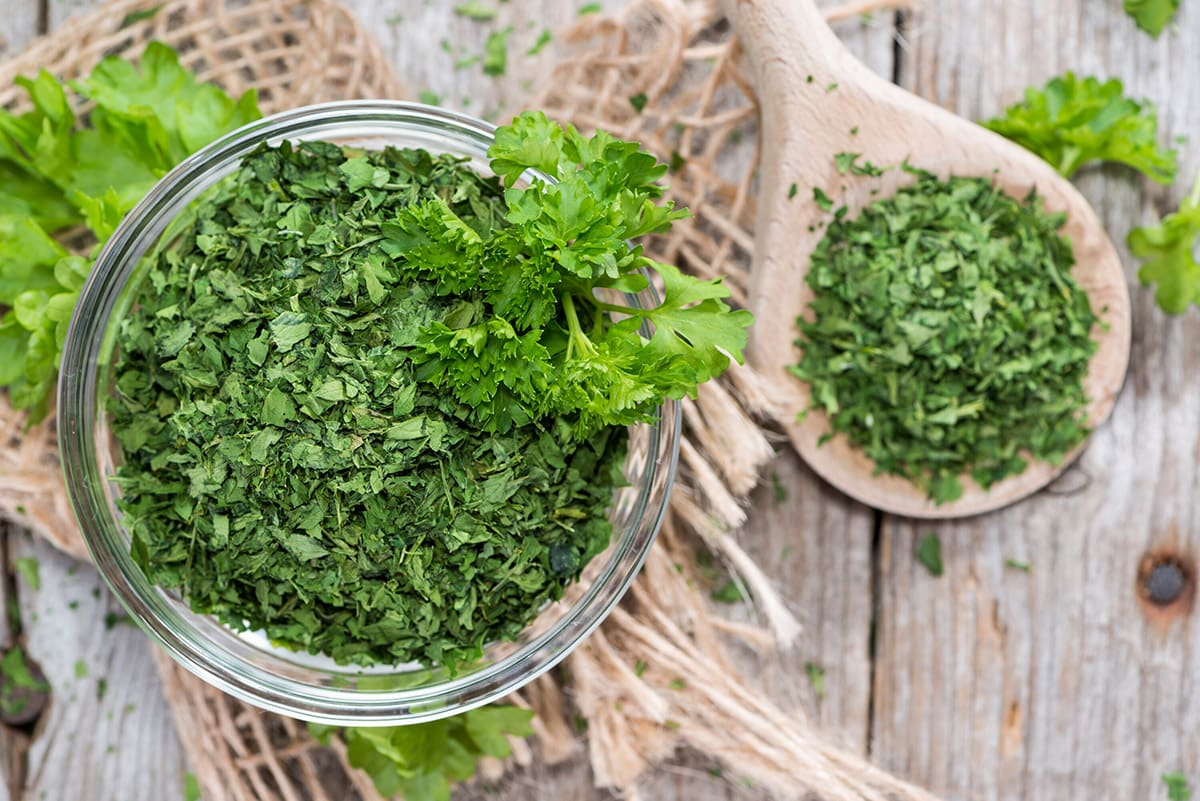 dried and fresh parsley in a glass jar and wooden spoon on a wooden background