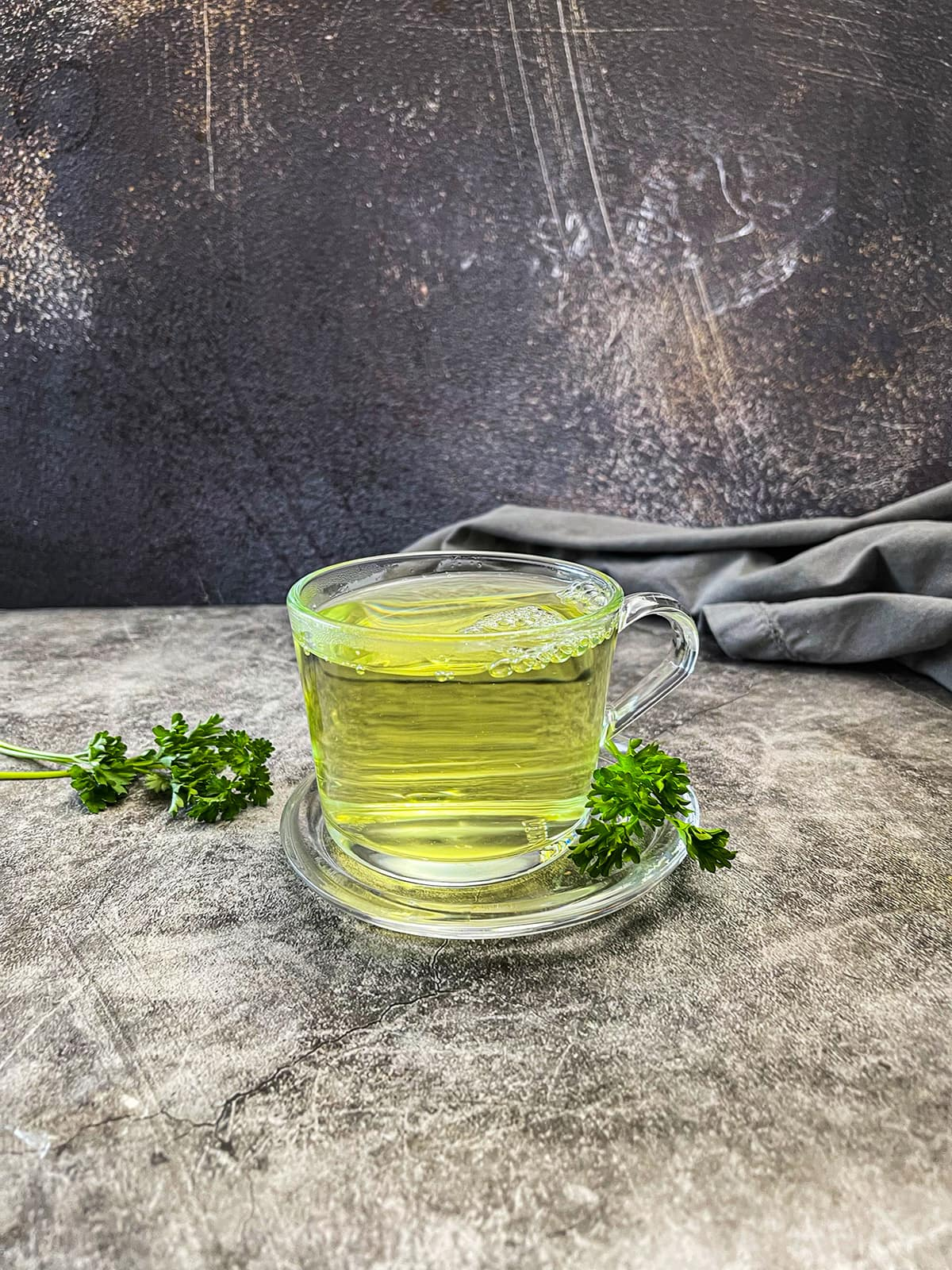 parsley tea from scratch in tea cup on a grey background
