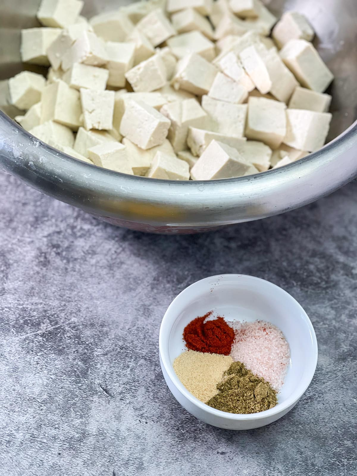 tofu with spices in a white bowl on a concete bad